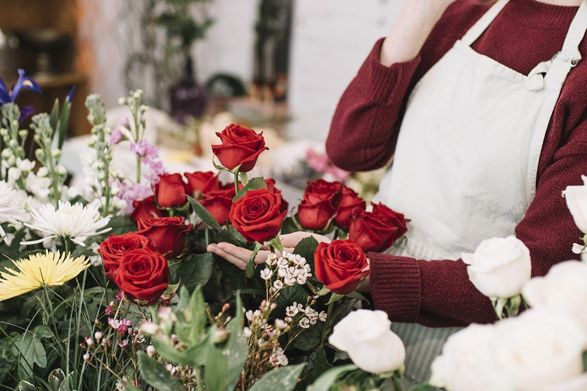 Un fleuriste devant un bouquet de roses rouges
